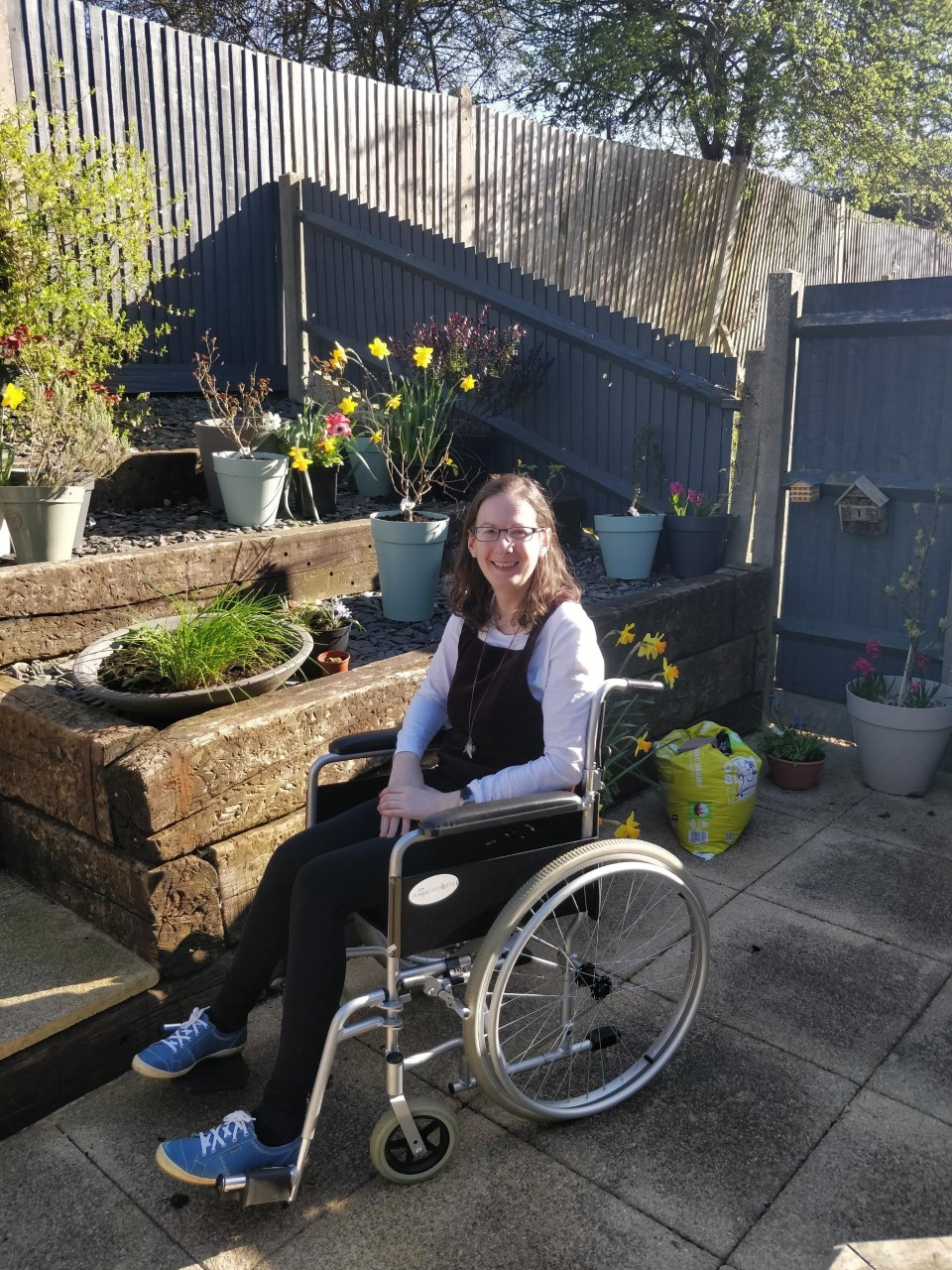 Angela Wright in her wheelchair in a garden